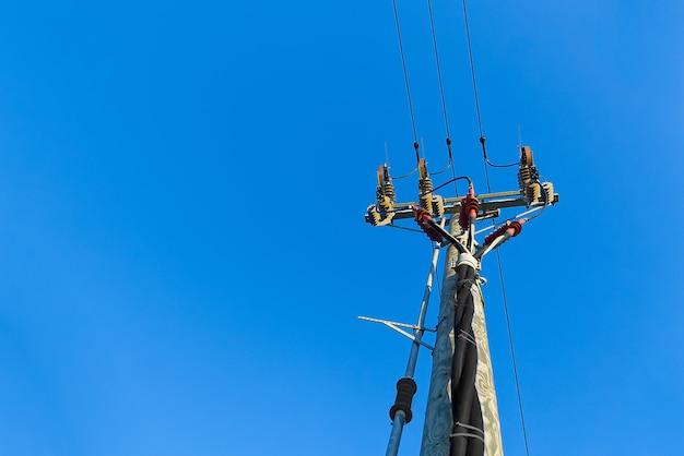 電力のスカイラインと木製の支柱の接続。青い空を背景に木製の電気ポスト
