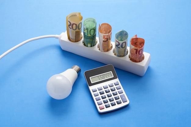 전구와 계산기가 있는 파란색 배경에 지폐가 있는 전력 스트립, 개념 지출 및 전기 절약