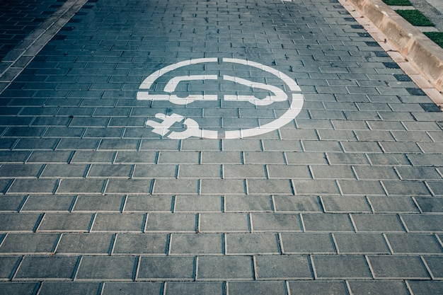 Electric recharging point for electric cars, evs that pollute less, painted on the ground.