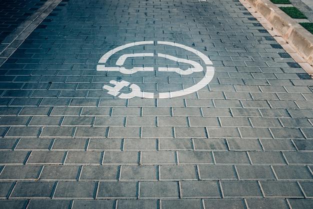 Точка подзарядки электромобилей, электромобили, которые меньше загрязняют окружающую среду, нарисованы на земле.