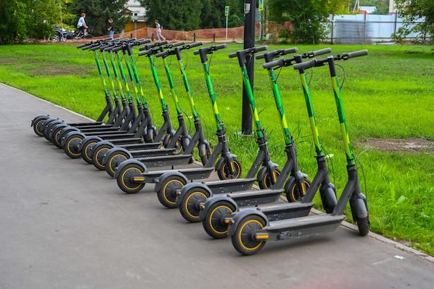 Электрический скутер парковка крупным планом. новый популярный транспорт для прогулок по городам и достопримечательностям. экологичный транспорт.