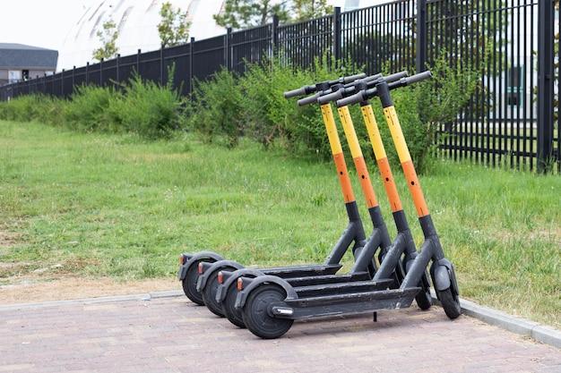 駐車場に並んでいる電動スクーター。シティバイクレンタルシステム、路上での公共キックスクーター