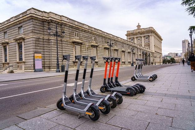 Electric scooters parked in a street in the royal palace of madrid. spain.