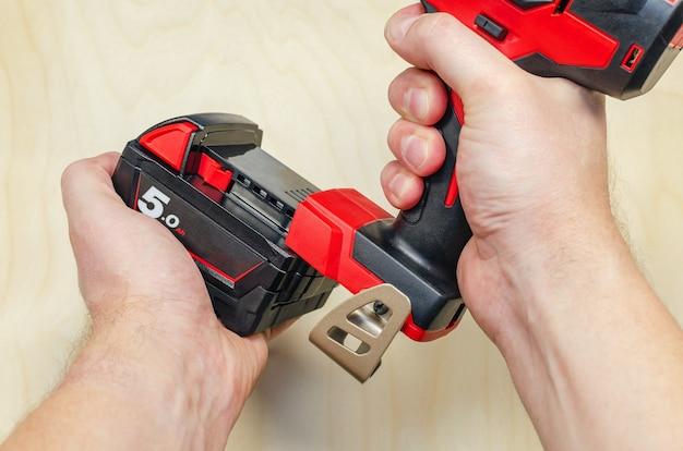 大工の手にあるバッテリーの電動ドライバー。男性の手は電動ドライバーを持っています。バッテリーの交換。