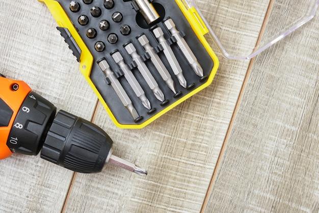 Электрическая отвертка, саморезы, отвертки, ящик для инструментов на деревянном фоне копировальное пространство