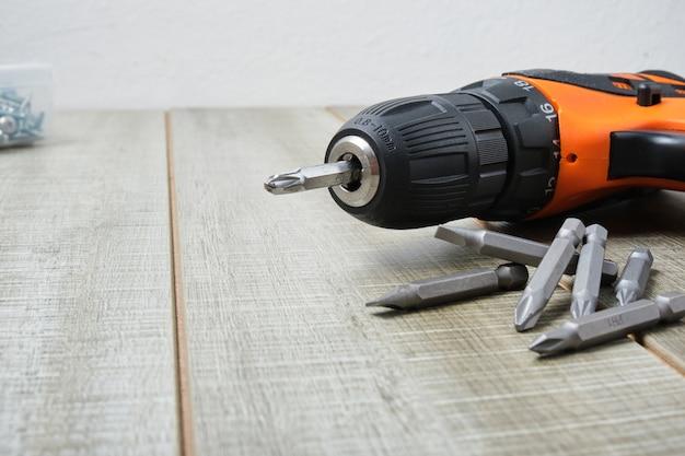 Электрическая отвертка, саморезы, насадки для отверток, ящик для инструментов на деревянной поверхности для копирования.