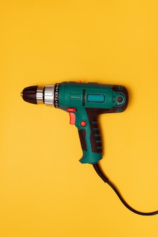 Electric screwdriver on a yellow background for construction work