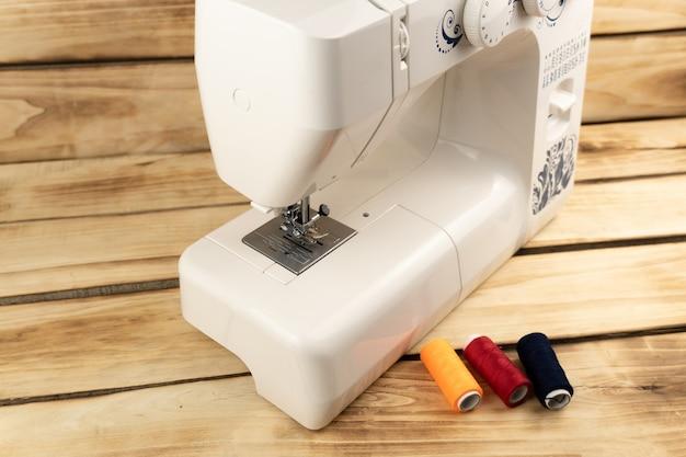 Электрическая швейная машина с швейными принадлежностями на деревянном фоне
