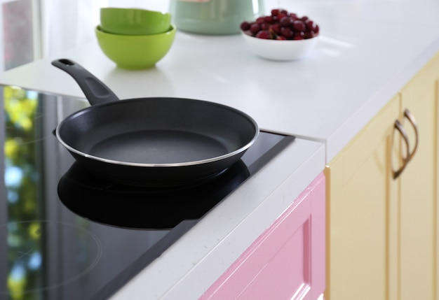Electric stove with frying pan in kitchen