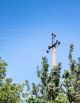 Electric support pole with ceramic elements against blue sky surface