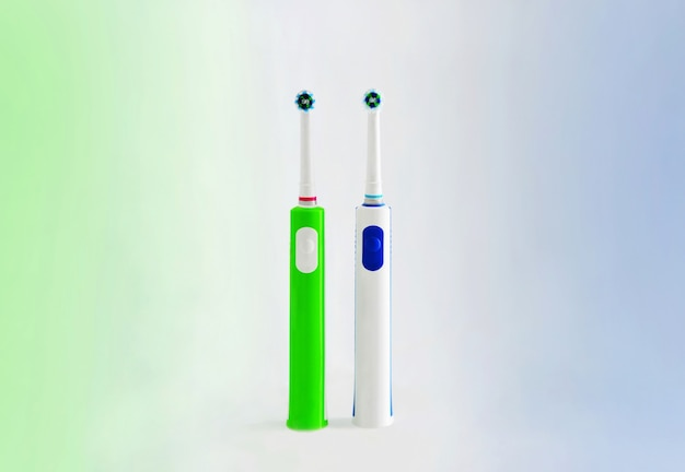Electric toothbrush isolated on a white background. green and blue electric toothbrushes stand on a green and blue background.
