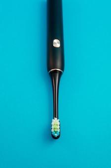 Электрическая зубная щетка на синем фоне