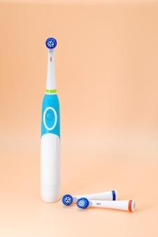 Электрическая зубная щетка с насадками на бежевом фоне
