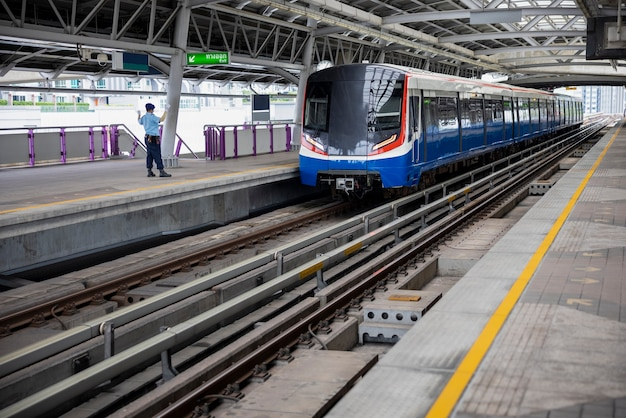 Электрический поезд и безопасность обратно, держась за руку на вокзале в таиланде