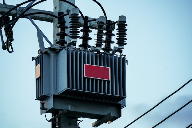 Electric transformer on pole with blue sky