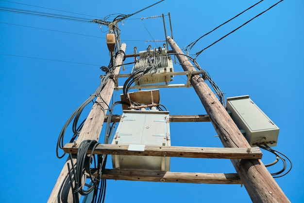 Electric transformer on wooden poles, blue sky background.