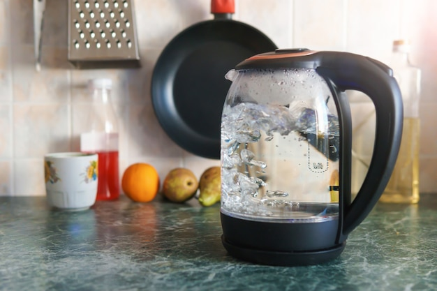 부엌에서 끓는 전기 투명 유리 주전자