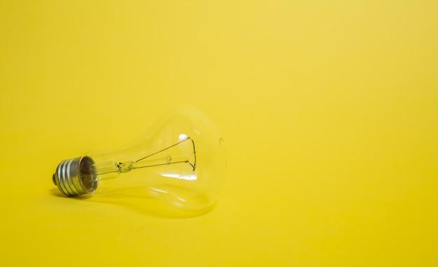 黄色の背景に電気の透明な電球