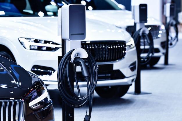 Зарядка электромобиля на станции с блоком питания, подключенным к электромобилю, заряжающемуся синим тоном