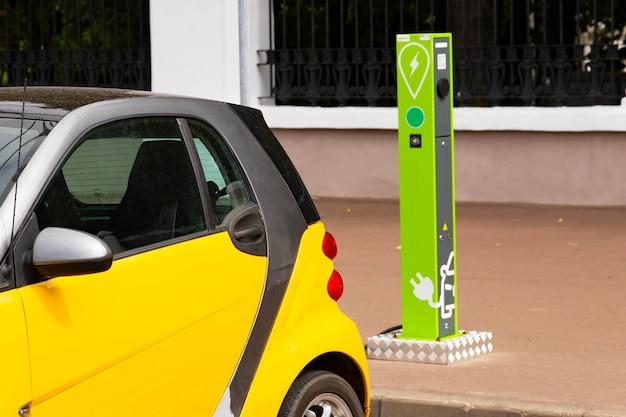 전기 자동차 용 전원 플러그가있는 전기 자동차 충전소. nfc 결제. 똑똑한 에너지. 자동차 배출에 의한 생태 및 환경 오염의 개념.