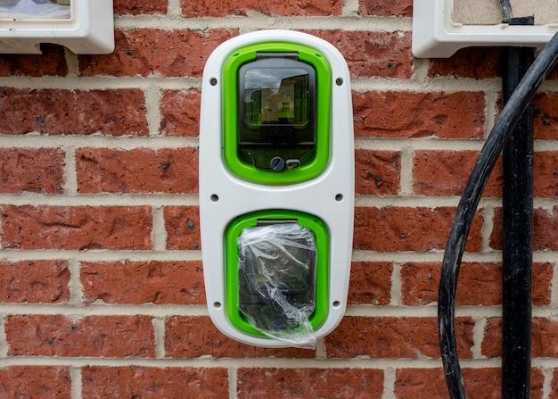 Бытовая точка подзарядки электромобилей, установленная вне дома в новостройке в рамках программы зеленой энергетики