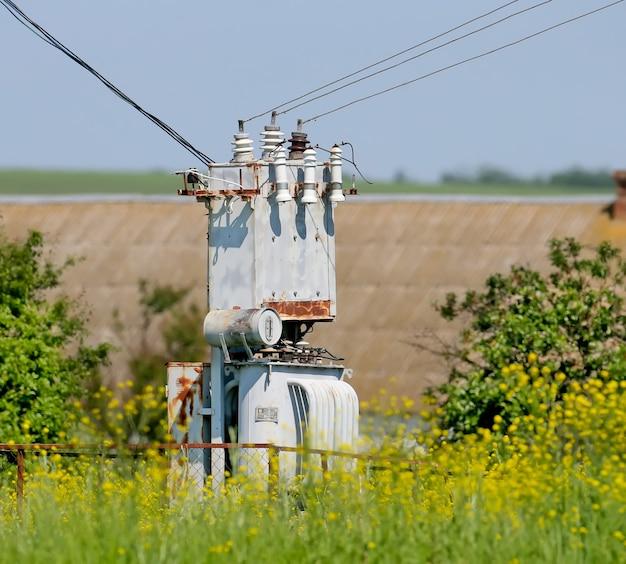 変圧器、顕花植物を背景にクローズアップ。田園風景
