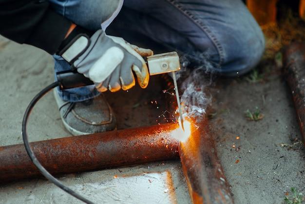 Электросварщик сваривает кусок металлической трубы