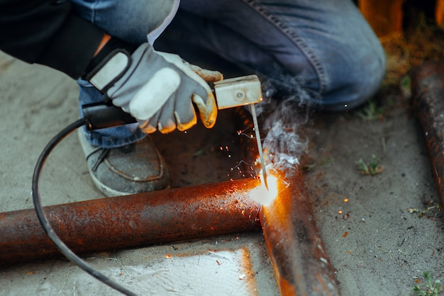 Electric welder welds a piece of metal pipe