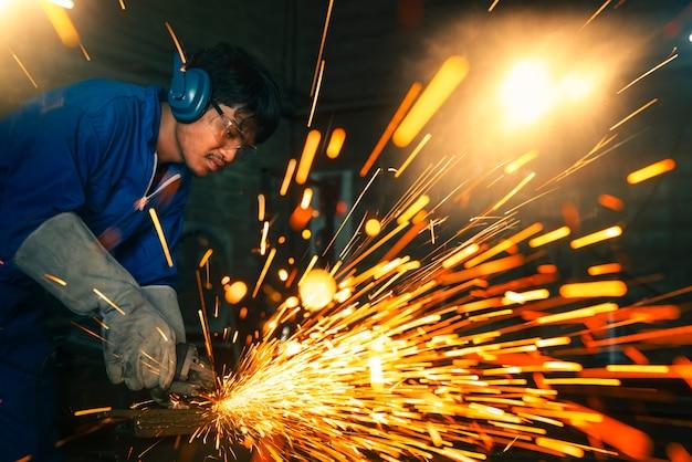 공장의 철골 구조에 전기 휠 연삭,이 이미지는 산업, 작업자 및 안전 개념에 사용할 수 있습니다.