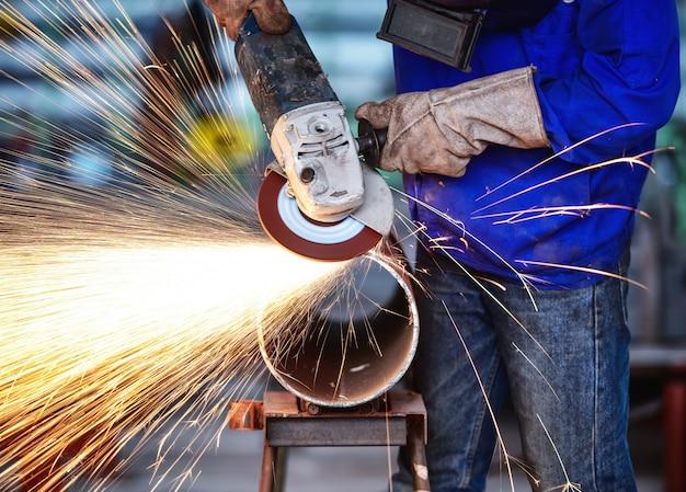 Electric wheel grinding on steel pipe in factory