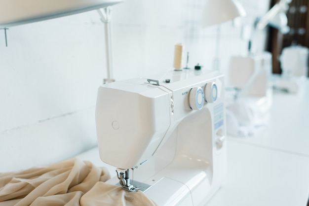 Electric white sewing machine with piece of beige fabric on desk inside workshop of contemporary seamstress or fashion designer