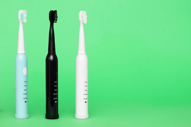 Electric wireless toothbrushes in blue black and white on a light green background copy space