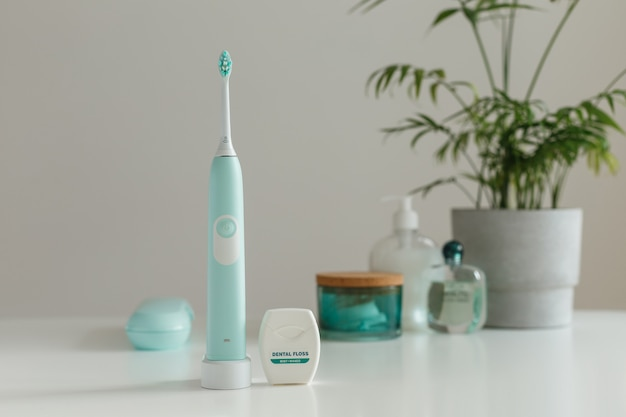 Electric wireless ultrasonic toothbrush with dental floss standing in bathroom