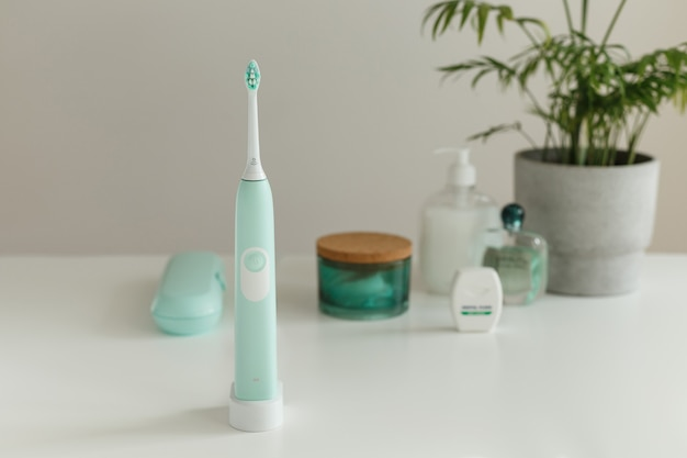 Электрическая беспроводная ультразвуковая зубная щетка с зубной нитью, стоящая в светлой ванной комнате