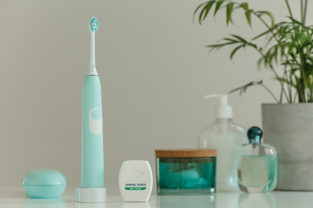 Electric wireless ultrasonic toothbrush with dental floss standing in light bathroom
