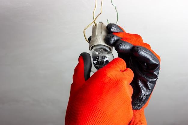 전기 마법사는 오래된 전구를 변경합니다.