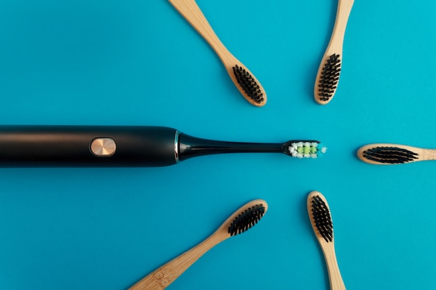 Electric and wooden toothbrush on blue background