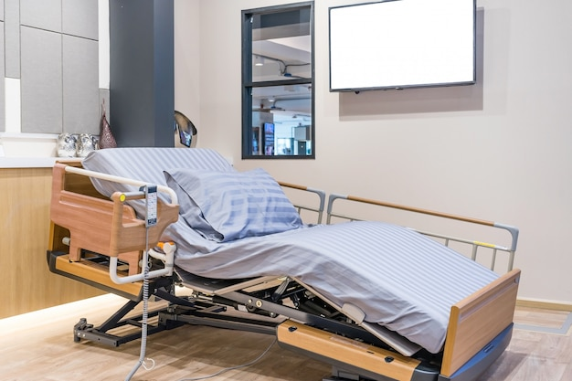 Electrical adjustable patient bed in hospital room.