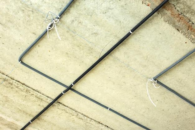 Электрические кабели, проложенные в защитной гофре, устанавливаются на потолке и стене в строящемся помещении.