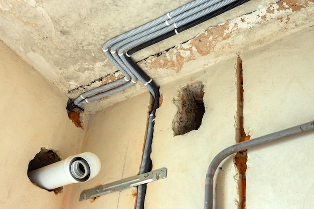 工事中の部屋の天井や壁に設置された保護波形に敷設された電気ケーブル。