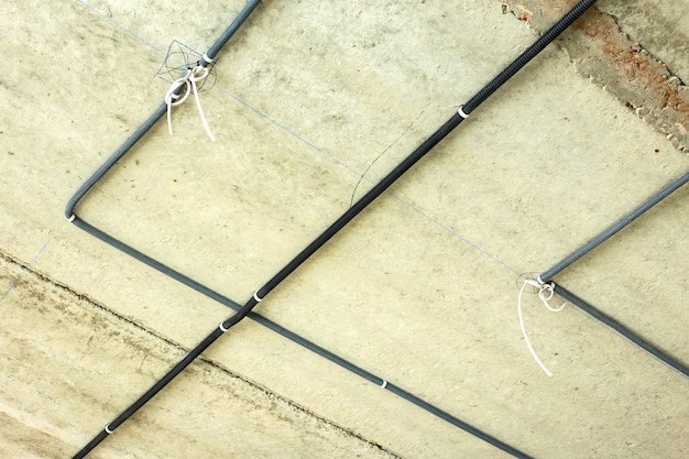 Electrical cables laid in protective corrugation installed on the ceiling and wall in a room under construction works.