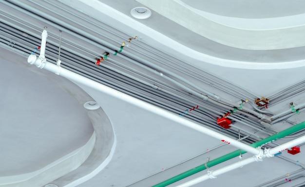 Система электропроводки и стальная оцинкованная труба электрического кабеля, установленная на потолке. автоматическая система пожаротушения с белой трубкой. строительство зданий. противопожарная защита и детектор.