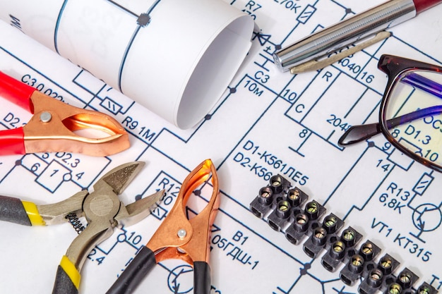 Electrical diagrams and metal pincers building a house concept for engineering projects Premium Photo