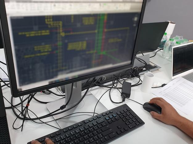 키보드와 마우스를 입력하여 컴퓨터 모니터에서 작업하는 전기 제도공 작업자