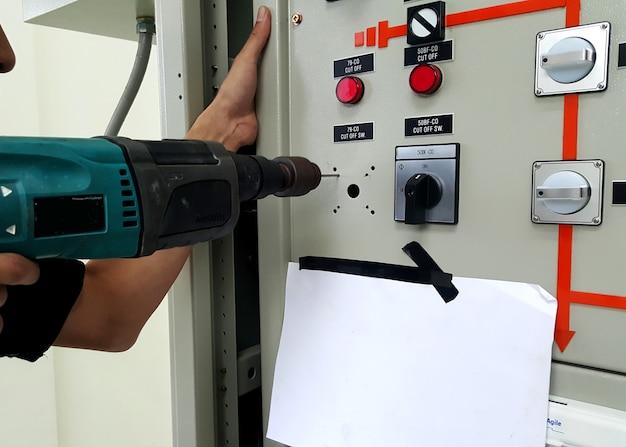 手に電気ドリルを持ち、新しいスイッチを変更するためにコントロールパネルの前に穴を開けます