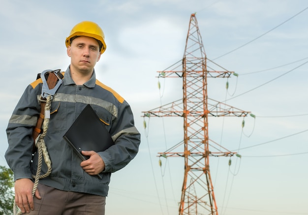 An electrical engineer on the background of a power line