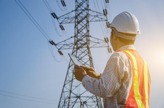 고전압 타워 배경이 있는 디지털 태블릿을 들고 사용하는 전기 엔지니어