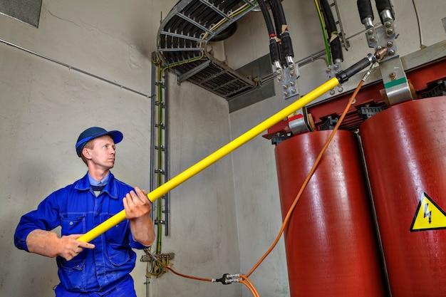 Инженер-электрик накладывает временное заземление на понижающий силовой трансформатор, чтобы обеспечить безопасность использования изоляционного стержня.
