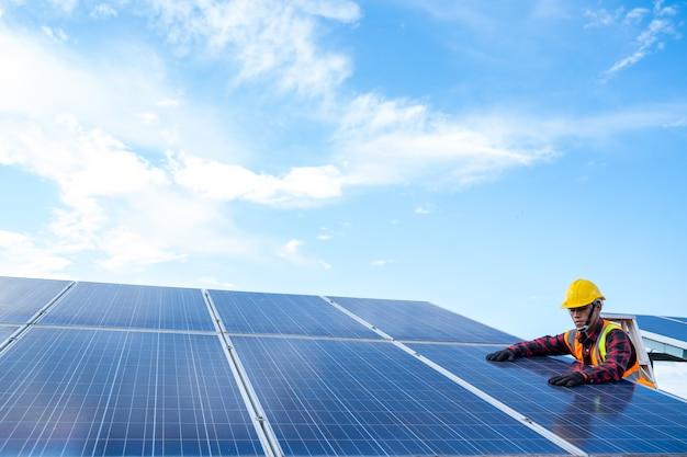 Инженер-электрик или техник, обслуживающий электрическую систему, работающий над проверкой и обслуживанием оборудования на солнечной электростанции, концепция чистой и зеленой альтернативной энергии.