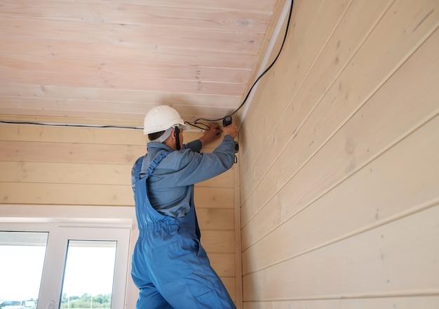 전기 엔지니어가 새로운 목조 별장에 전기 배선 설치를 수행합니다.